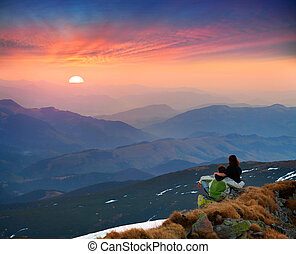 The young couple meets the sunrise in the mountains