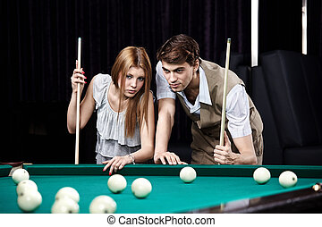 The young couple plays billiards