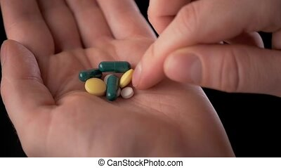 The young doctor with a hand full of pills. A lot of drugs in man hand.