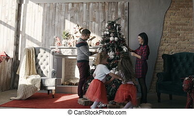 The young family adorns a Christmas tree. Two little sisters dressed in the same clothes run around a Christmas tree decorated by their young parents