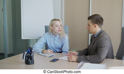 The young female student has a consultation with her male supervisor in his office.