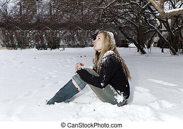 The young frozen woman under the falling snow.