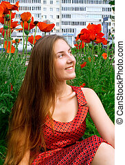 girl against a lawn with red poppies