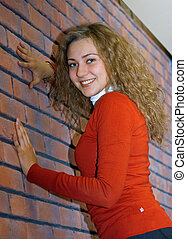 girl against red brick wall