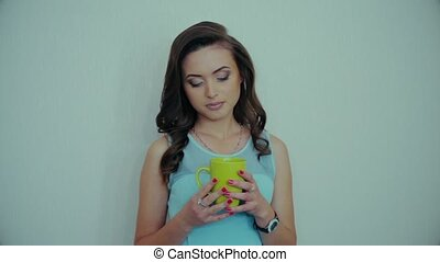 The young girl drinks coffee