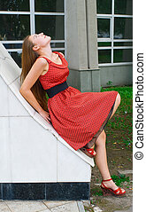 girl in red dress against building