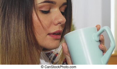 The young girl is drinking from a mug