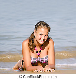 The young girl lays in at sea coast