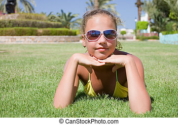The young girl lays on a grass