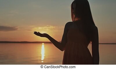 The young girl releases the sun from her hands. Beautiful romantic sunset.