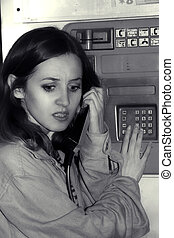 young girl talking in public pay telephone