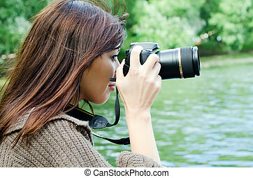 The young girl with the camera in park