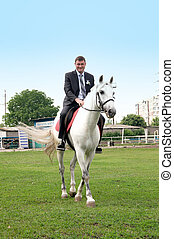The young groom riding on a white horse