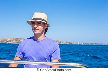 The young man at the helm of small boat