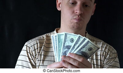 the young man believes and holds dollar bills fanned out with happy face