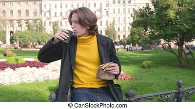 The young man drinks coffee and eats sweet cake in the park, he smiles, is dressed in a yellow sweater and black raincoat or jacket, Jeans trousers, flowers and green grass on background