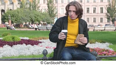 The young man drinks coffee and eats sweet cake in the park...