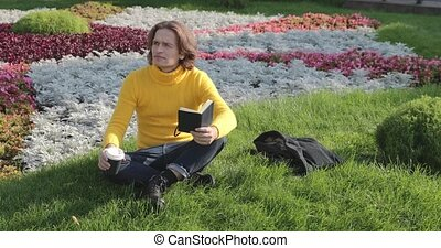 The young man drinks coffee and reads the book in the park, he smiles, has a rest, is dressed in a yellow sweater, flowers and grass on background