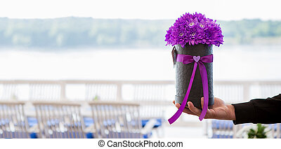 The young man gives a bunch of purple chrysanthemums.