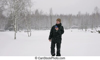 The young man goes in a winter forest in the snow and is oriented over the phone. He is looking for the right direction on the electronic map.