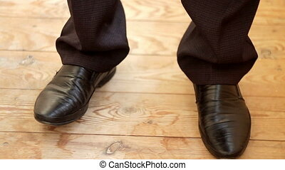 the young man in black pants and shoes tapping in the...