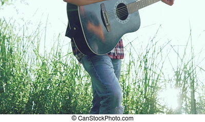 The young man in hat playing the guitar near the pond. Slowly