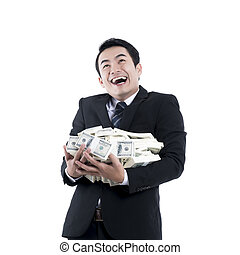 The young man laughing and holding a big pile of money