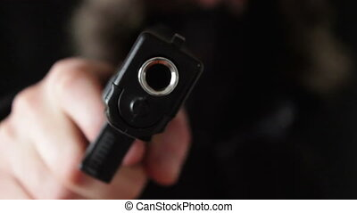 the young man points the gun at the camera,black background