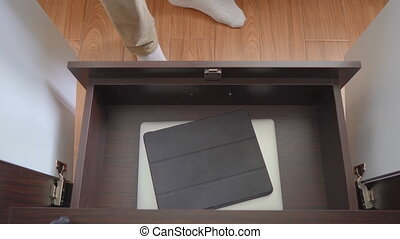 The young man puts all his electronic devices in a closet. ...