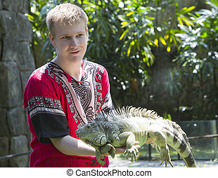The young man, the teenager holds an iguana on hands