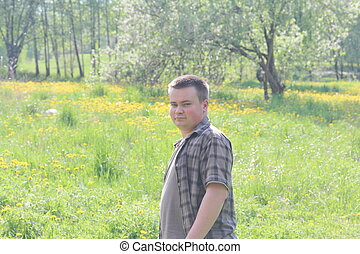 The young man turned back, walking along a spring meadow with lush young grass. Shot in backlight.