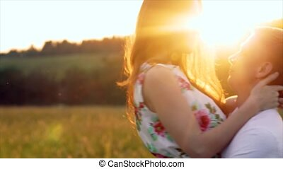 The young man turns a girl on the sunset, the sun's rays seep through them.