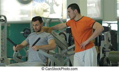 The young man under his fitness trainer doing exercise