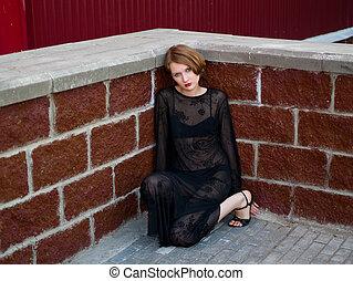 sad girl in black dress against red brick wall