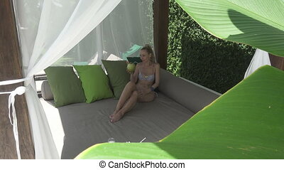The young slender woman has a rest in the tropical resort...