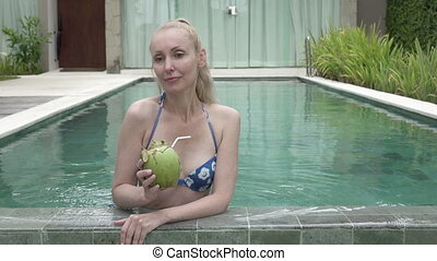 The young slender woman in Bikin drinks coconut milk from a coco on the edge of the pool in the tropical resort