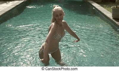 The young slender woman in bikini with a long fair hair...