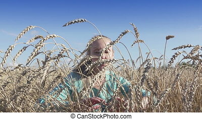 The young slender woman with a long fair hair moves apart hands stalks of ripe wheat in sunny day