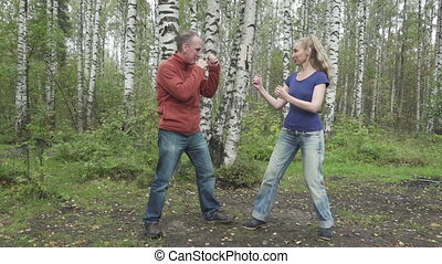 The young slender woman with long svetly hair in a t-shirt and jeans and the man does fighting martial arts on a forest glade,slow motion