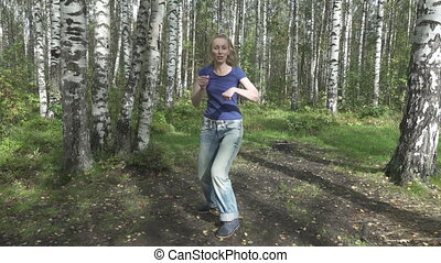 The young slender woman with long svetly hair in a t-shirt and jeans does fighting martial arts on a forest glade,slow motion