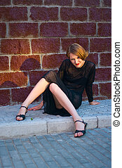 girl in black dress against red brick wall