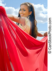 smiling girl in golden dress with red scarf
