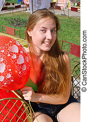smiling girl with a red balloon