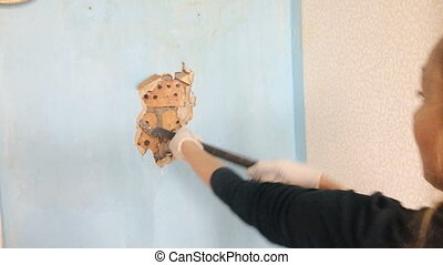 The young woman does repair in the apartment. The worker a hand tool breaks off an old wall covering under which the brick wall is visible