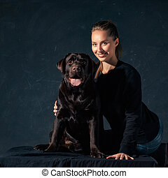 The young woman hugging a mix breed dog - The young woman...