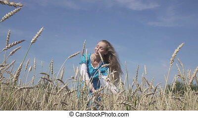 The young woman in a blue dress and with a long fair hair in the field of ripe wheat in sunny day,slow motion