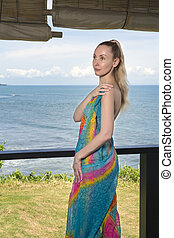 The young woman in a bright scarf pareo stand on a terrace and the sea on a background.
