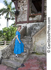 The young woman in a long blue dress on a ladder of the empty, abandoned house. Cuba.