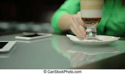 The young woman is holding the coffee cup sitting at the table with devices on the surface in the cafe.