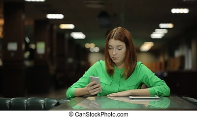 The young woman is sitting at the table and cafe working with the cell phone waiting for the order.